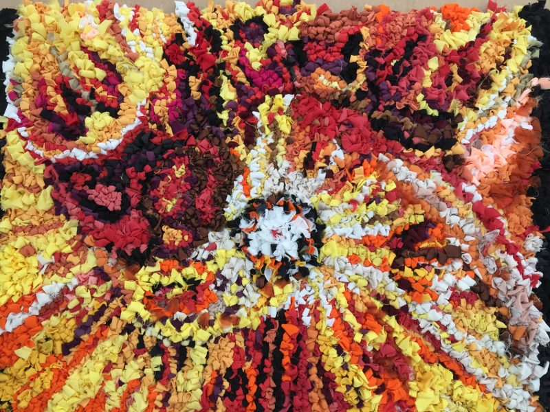 Image of a rag rug made from red and yellow fabric made by Alison Bailey Smith for an exhibition using Simon Sherry's images for The Eye Fund.