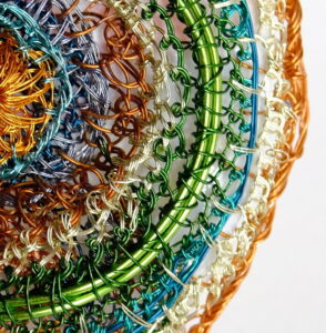 Detail of colourful stitches in round brooch made from recycled wire reclaimed from televisions and bought lacquered copper and aluminium wire, made by Alison Bailey Smith